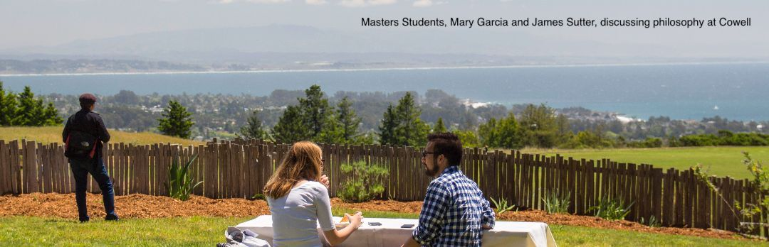 two students sit at a picnic table overlooking the campus and Monterey Bay, a third student stands to the left