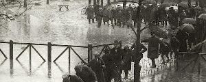 men wait in line to cross a flood by stepping from chair to chair
