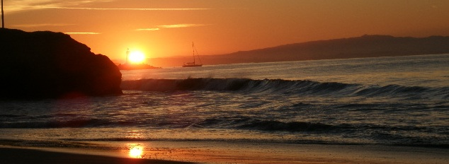 Monterey Bay: sunrise at the San Lorenzo River mouth, in the distance a sailboat leaves the harbor